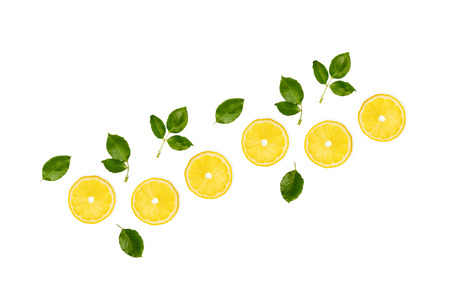 Yellow lemon slices and leaves isolated on white background, top view. Lemon citrus vitamin c concept, summer bright composition.