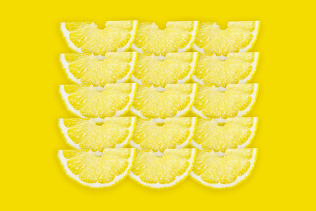 Fresh lemon half slices pattern on yellow background, top view. Summer bright background, citrus fruit pieces, vitamin freshness concept.