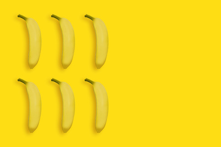 Yellow bananas on yellow background, top view. Summer bright background, sweet tropical fruit concept with space for text.