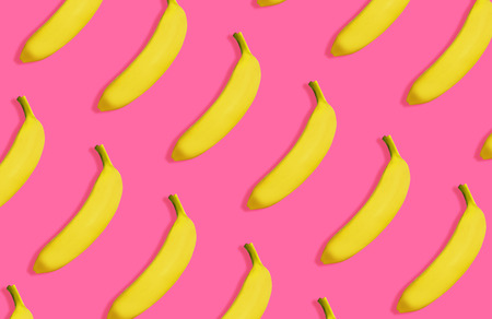 Yellow bananas pattern on vivid pink background, top view. Summer bright image, sweet tropical fruit concept, repetitive minimalist objects.