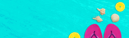 Summer time wide banner, purple flip flops, seashells and lemon pieces on vivid blue grunge background with space for text.