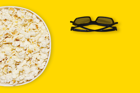 Popcorn in carton bowl and 3d cinema glasses on yellow background with space for text top view, bright summer concept. Banque d'images