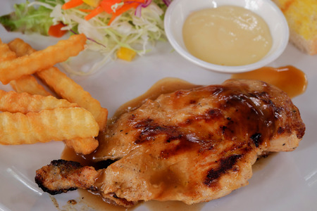 Close up of chicken steak in dish on the wood table.