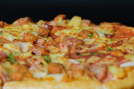 odorous: Close up of super deluxe pizza on black background.