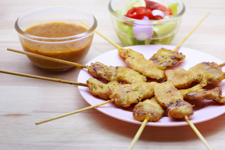 gill: Pork satay and sauce on wood background. Stock Photo