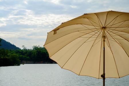 edge: The brown umbrella at edge the river.
