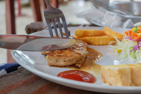 odorous: Close up of cut the chicken steak in dish on the wood table. Stock Photo