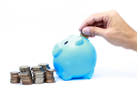 Man dropping a coin into the piggy bank on white background.