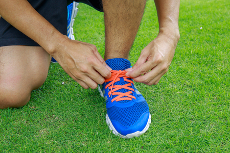 pace: The man lacing the shoes on green lawn. Stock Photo
