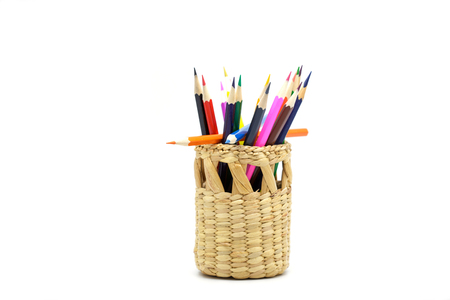 Color pencils in wicker basket on white background.