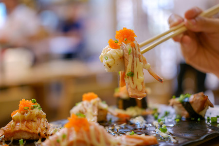 spawn: Chopsticks gripping Sushi salmon from the tray. Stock Photo