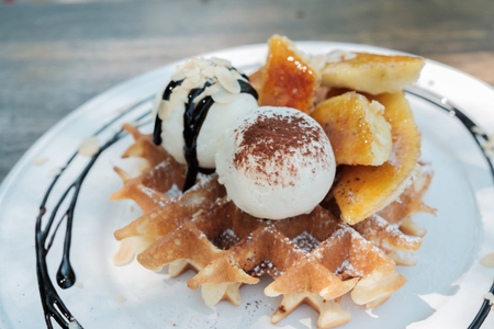 Close up of ice cream and waffle in dish.