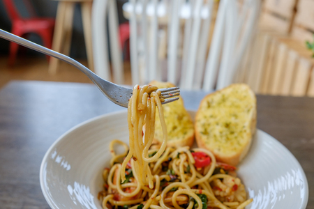 Closeup of hand scooping spaghetti with fork on the wood table. Stock Photo