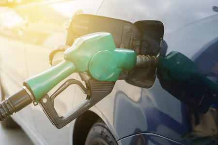 benzene: Car refueling in filling station in the warm light. Stock Photo