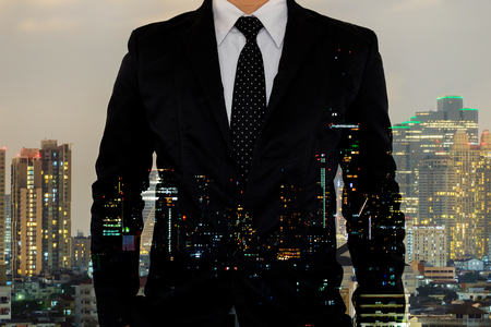 Double exposure of businessman on night cityscape background.