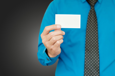 Closeup card in right hand of blue shirt businessman on gray background.