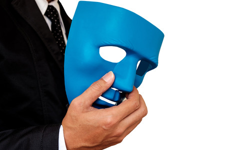 insincere: Businessman holding blue mask in hand on white background. Stock Photo