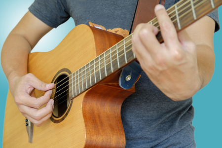 entertainers: Man playing guitar on blue background. Stock Photo
