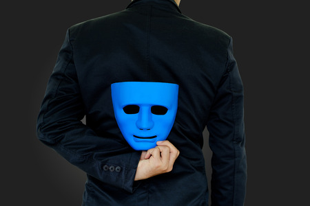 The businessman hides the mask in the hand behind his back on black background.