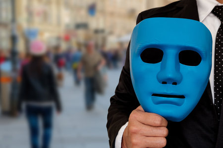 insincere: Businessman prepare to wear a mask to go out to society. Mask in hand of businessman.