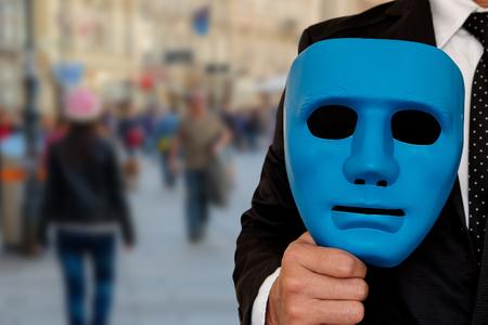 El hombre de negocios se prepara para usar una máscara para salir a la sociedad. Máscara en la mano de hombre de negocios. Foto de archivo