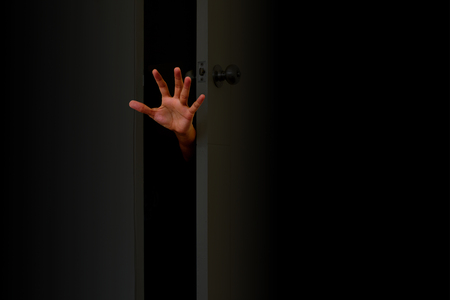 The hand protrudes from the outside of the door in the dark. Concept of Halloween.