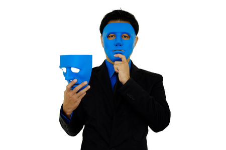 Businessman wearing blue mask and holding another blue mask in hand on white background with clipping path. Stock Photo