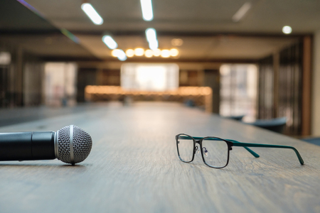 Microphone and eyeglasses on table. Concept of something for say and something for look. Stock Photo