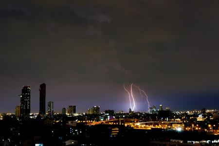 Lightning strikes down the city in darken night.