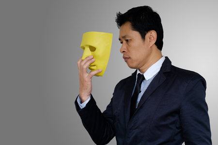 Asia businessman is wearing yellow mask on gray background with clipping path.