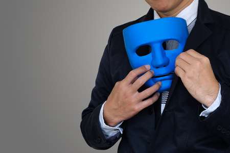 Businessman is hiding blue mask in your suit on gray background  and copy space