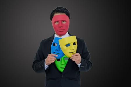 Businessmen wear red mask and hide many masks in suit on black background 版權商用圖片