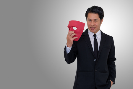Businessman holds a mask and smiles with hypocrisy on gray background  and copy space. Stock Photo