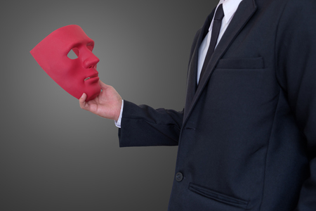Businessman holding red mask in hand on gray background with clipping path.