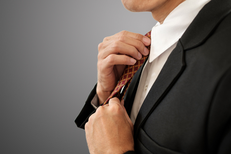 Businessman set his necktie on gray background with clipping path. Imagens