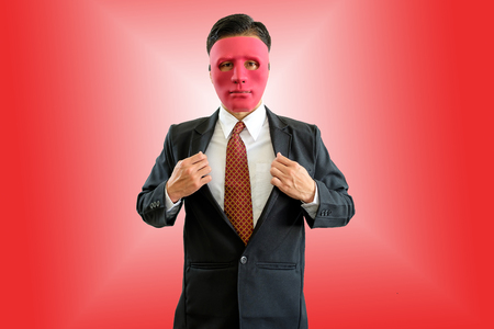 Businessman wearing red mask on red background with clipping path.