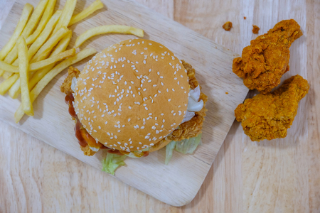 Top view of chicken hamburger and fried chicken on wooden background.