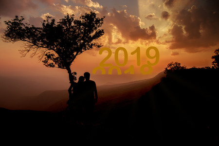 Silhouette of two people looking new year 2019 replacing old year 2018.