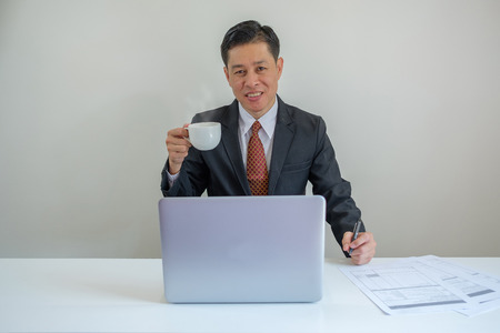 Businessman smiles and holding a cup of coffee when he working in the office. 版權商用圖片