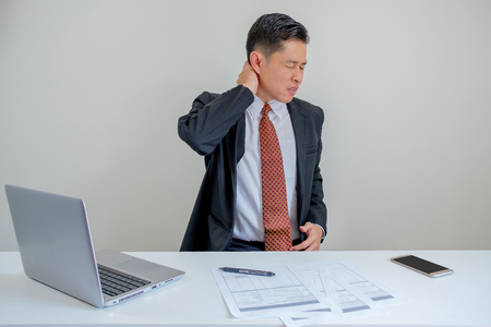 Businessman hurts his neck when he working in the office.