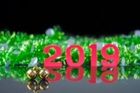Closeup double golden circle ornaments on reflex floor with background of new year 2019.