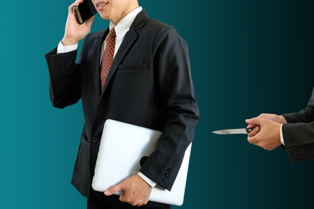 Businessman holds laptop and speaking telephone together with another man holding knife to hurt with clipping path.