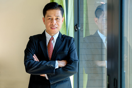 Handsome businessman in black suit smiles and standing in the office.