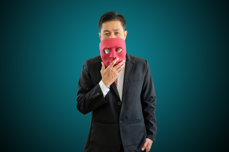 Asia businessman is wearing red mask on geen background with clipping path. 版權商用圖片