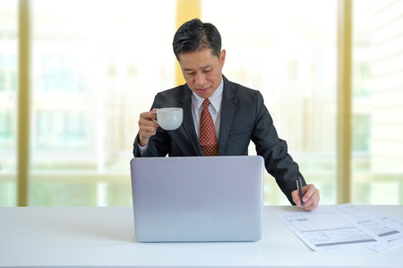 Businessman drinking coffee when he works in the office.