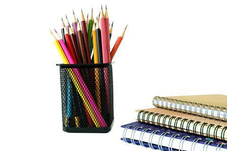 Pencil in in steel grille box and three notebooks on white background. 版權商用圖片