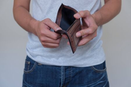 Man opens the empty wallet on gray background.