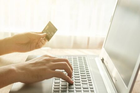 Hands of someone paying with credit card for buy something in internet on warm light.