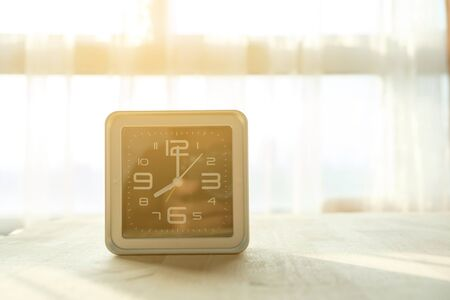 There is a clock put on the table in a sunshine day.