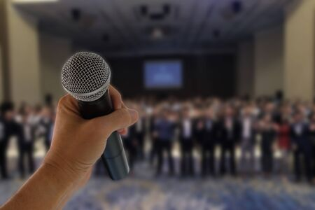 There is a hand hold a microphone ready to speak before many people in seminar event  版權商用圖片
